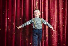 作为小丑打扮的男孩执行在阶段 免版税库存照片