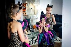 作为巫婆假装的作为老虎和两个女孩在f蠕动 图库摄影