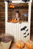 作为巫婆打扮的小女孩卖南瓜 库存照片