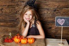 作为巫婆打扮的小女孩卖南瓜 免版税库存照片