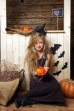 作为巫婆打扮的小女孩坐南瓜 万圣夜的概念 免版税库存照片