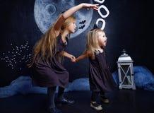 作为巫婆打扮的小女孩惊吓和捉住她的姐妹 库存图片