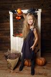 作为巫婆打扮的小女孩攻击用南瓜 免版税库存图片