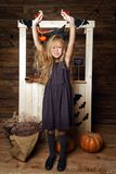 作为巫婆打扮的小女孩攻击用南瓜 库存图片