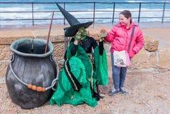作为巫婆打扮的节日的参加者给女孩糖果 免版税库存照片