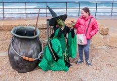 作为巫婆打扮的节日的参加者给女孩糖果 免版税库存图片