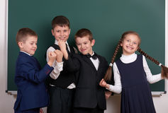 作为帮会的小组学生,摆在空白的黑板背景,做鬼脸和情感附近,穿戴在经典黑衣服 库存图片