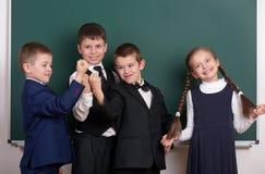 作为帮会的小组学生,摆在空白的黑板背景,做鬼脸和情感附近,穿戴在经典黑衣服 免版税库存图片