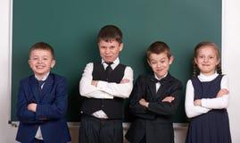 作为帮会的小组学生,摆在空白的黑板背景,做鬼脸和情感附近,穿戴在经典黑衣服 免版税库存照片
