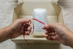 作为弓的妇女举行红色丝带在泡影板料的礼物的在箱子 库存图片