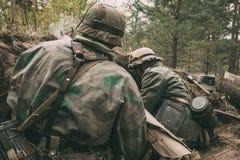 作为德国人Wehrmacht二战暗藏的开会的步兵战士穿戴的再enactors 库存照片