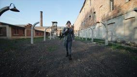 作为德国士兵打扮的一名年轻英俊的男性演员走向照相机 集中营的重建 股票录像