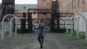 作为德国士兵打扮的一名年轻英俊的男性演员走向照相机 集中营的重建 影视素材