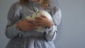 作为德雷库拉新娘打扮的女孩握一块独眼的头骨 灰色颜色范围 死者的天, hallowen 影视素材