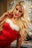 作为性感的圣诞老人帮手穿戴的美好的白肤金发的女性模型 免版税图库摄影