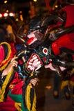 作为恶魔打扮的人们跳舞在街道 库存照片