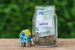 作为房子被标记的玻璃瓶子瓶以充分硬币和miniatu 库存照片