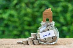 作为房子被标记的玻璃瓶子瓶以充分硬币和miniatu 免版税库存照片