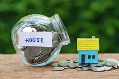 作为房子被标记的玻璃瓶子瓶以充分硬币和miniatu 免版税库存图片