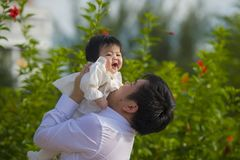 作为拿着她的在花园前面的甜矮小的女婴的父亲的年轻愉快和骄傲的人女儿在度假胜地 免版税库存图片