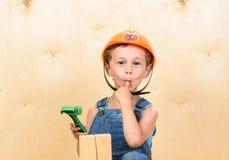 作为握在嘴的滑稽的建造者的孩子男孩手指在击中它以后与锤子 图库摄影