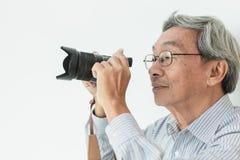 作为摄影师的亚洲老人玻璃退休爱好采取摄影 免版税库存图片