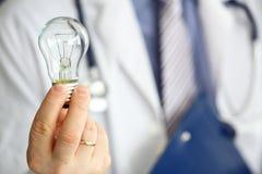 作为明亮的想法发明标志的男性医生手藏品电灯泡 图库摄影