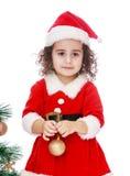 作为有一个玩具的圣诞老人打扮的女孩在 免版税库存照片