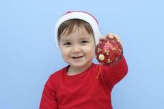 作为有一个红色中看不中用的物品的圣诞老人打扮的一个小孩的档案在他的手上 图库摄影