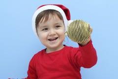 作为有一个红色中看不中用的物品的圣诞老人打扮的一个小孩的档案在他的手上 免版税库存照片