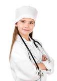 作为有听诊器的一位医生打扮的可爱的小女孩 免版税库存照片