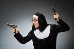 作为有手枪的尼姑打扮的人 免版税库存图片