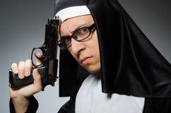 作为有手枪的尼姑打扮的人 免版税库存照片