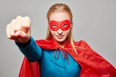 作为有握紧拳头的一个超级英雄打扮的妇女 免版税库存照片