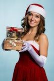 作为有礼物的圣诞老人打扮的美丽的女孩 免版税图库摄影