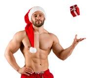 作为有红色帽子和小礼物盒的圣诞老人打扮的坚强的成人健身人,被隔绝在白色背景 库存图片