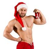 作为有红色帽子和小礼物盒的圣诞老人打扮的大力士,被隔绝在白色 免版税库存图片
