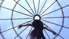 作为杂技演员在圆环的一个壮观的姿势转动空中杂技的女孩的底视图 股票录像