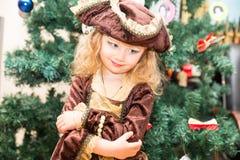 作为海盗打扮的小女孩孩子为在圣诞树背景的万圣夜  免版税图库摄影