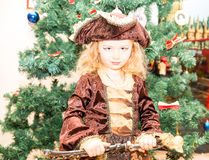 作为海盗打扮的小女孩孩子为在圣诞树背景的万圣夜  免版税库存图片