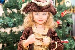 作为海盗打扮的小女孩孩子为在圣诞树背景的万圣夜  免版税库存照片