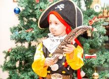 作为海盗打扮的小男孩孩子为在圣诞树背景的万圣夜  免版税库存照片
