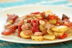 作为温暖油煎的土豆沙拉的蕃茄 免版税库存图片