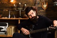 作为爱好的吉他 舒适温暖的大气戏剧喜爱音乐的人 有胡子的人拿着黑电吉他 人 免版税库存照片