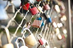 作为爱诺言,恋人关闭沿桥梁的挂锁 图库摄影