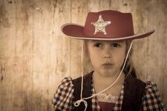 作为牛仔/女牛仔打扮的逗人喜爱的孩子 图库摄影
