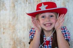 作为牛仔/女牛仔打扮的逗人喜爱的孩子 库存图片
