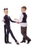 作为猫打扮的跳舞的小女孩和格子花呢披肩的一个男孩授予 免版税库存图片