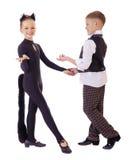 作为猫打扮的跳舞的小女孩和格子花呢披肩的一个男孩授予 库存图片