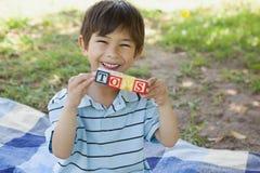 作为玩具的愉快的男孩藏品块字母表在公园 免版税图库摄影